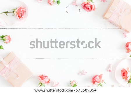 Flowers composition. Gifts and rose flowers on white wooden table. Women Day. Flat lay, top view