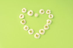 Flowers composition. heart frame of white small rose on green background. Mother's day, Valentine's day, birthday, spring, summer concept. Flat lay, top view, copy space