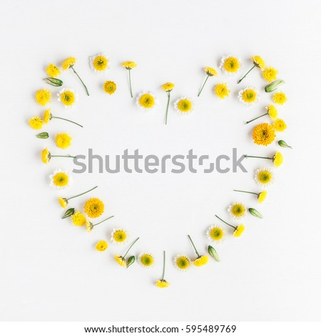 Flowers composition. Heart symbol made of various yellow flowers on white background. Flat lay, top view - Shutterstock ID 595489769