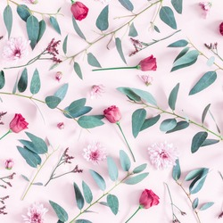 Flowers composition. Pattern made of pink flowers and eucalyptus branches on pink background. Flat lay, top view, square.