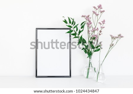 Flowers composition. Photo frame, pink flowers, green leaves on white background. Front view, copy space, mock up