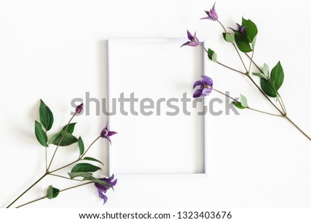 Flowers composition. Purple flowers, photo frame on white background. Spring, easter concept. Flat lay, top view, copy space