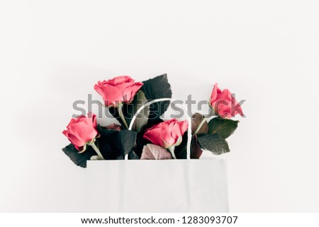Flowers composition. Tender pink rose in white paper bag. Valentine's Day. Birthday, Happy Women's Day. Flat lay, top view, copy space #1283093707