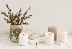 Flowers composition. White candles and willow branches on white wooden background. Spa