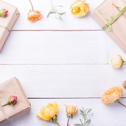 Flowers composition with gifts and rose flowers on white wooden table. Flat lay, top view. Copy space. Birthday, Mother's, Valentines, Women's, Wedding Day concept.
