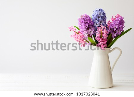 Stock Photo Flowers composition with lilac and pink hyacinths. Spring flowers in vase on white background.