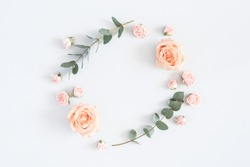 Flowers composition. Wreath made of rose flowers, eucalyptus branches on pastel gray background. Flat lay, top view, copy space