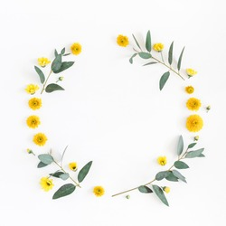 Flowers composition. Wreath made of various yellow flowers and eucalyptus branches on white background. Flat lay, top view, copy space, square.