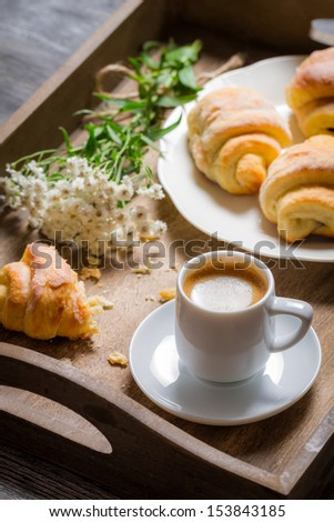 Flowers, croissant and coffee for breakfast