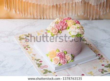 flowers decorate buttercake and buttercream around for wedding Birthday Newyears Valentine's Day and festive on white table closeup copyspace