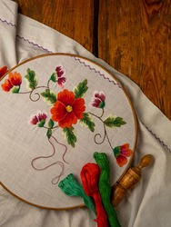 Flowers embroidery on white textile in hoop wooden background. Traditional ukrainian floss stitch embroidery motifs. Handmade ethnic clothes towel tablecloth. New normal lockdown hooby crafts tutorial