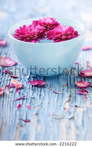flowers floating in water in bowl sitting on weathered wood