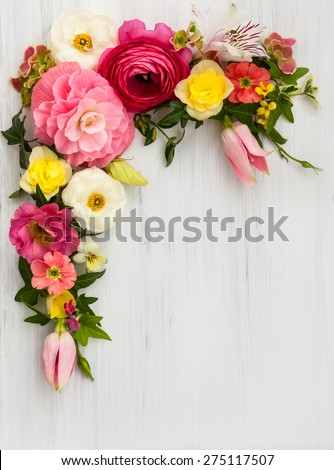 Flowers frame on white wooden background. Top view with copy space