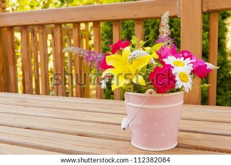 Flowers from the garden in pink bucket vase