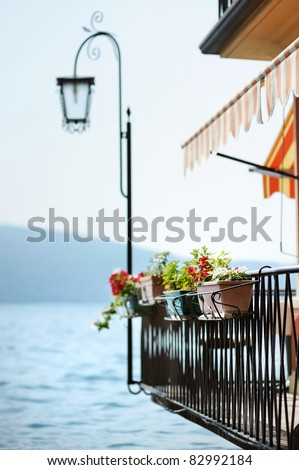 Flowers hanging on a balcony by Garda lake