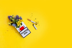 flowers in a cigarette pack, a broken cigarette on a yellow background. creative concept. world no tobacco day. no smoking