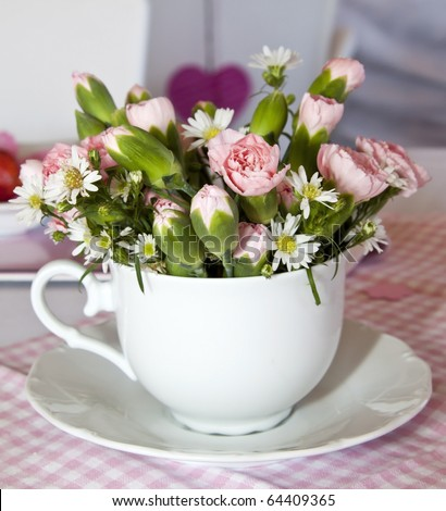 Flowers in a cup on a pink and white table