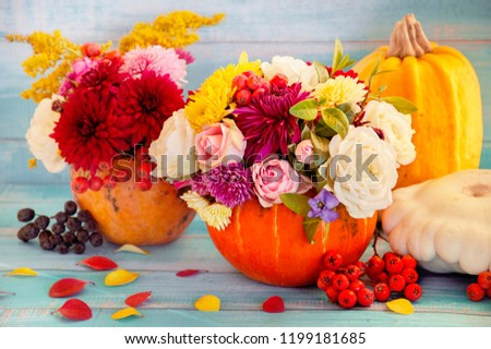 Flowers in a pumpkin. Bright autumn background. Colorful autumn card. Pumpkin with fresh flowers. Autumn flower arrangement. #1199181685