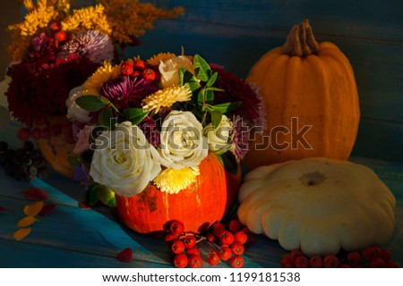 Flowers in a pumpkin on a background of sunlight. Bright autumn background. Colorful autumn card. Pumpkin with a bouquet of flowers. Flower arrangement for Halloween. #1199181538