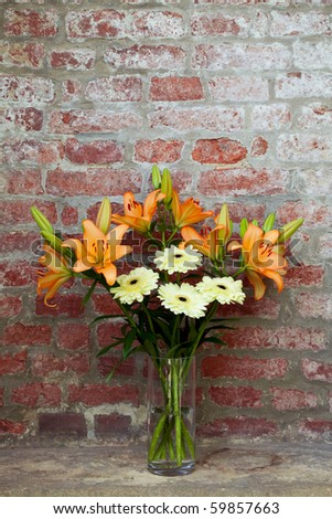 flowers in a vase standing in the background of a brick wall