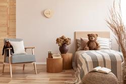 Flowers in brown vase on wooden nightstand table next to single bed with stripped bedding with teddy bear