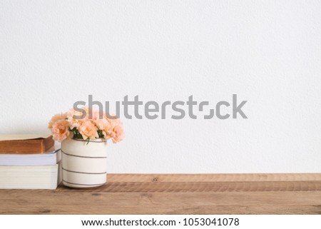 Flowers in vase and  book on wooden table with copy space.home decor