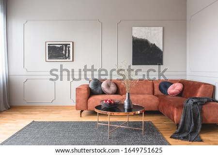 Flowers in vase and red fruits in bowl on wooden coffee table in elegant living room interior with ginger sofa