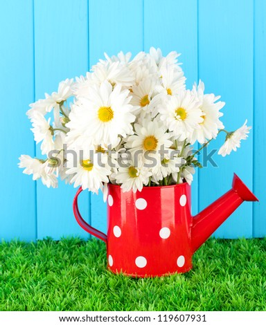 Flowers in vase on grass on blue background