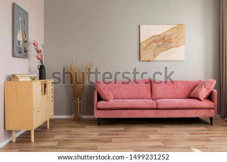 Flowers in vases on wooden commode in contemporary living room interior with pastel pink sofa #1499231252