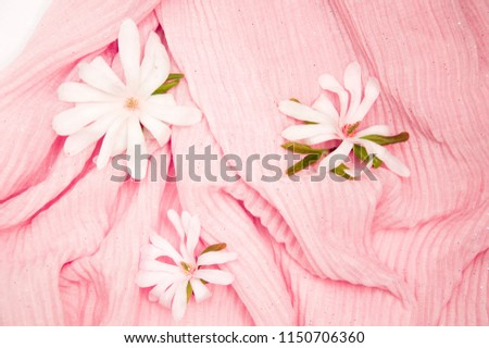 flowers of a magnolia on a gently pink crimped dress close-up, gentle background #1150706360