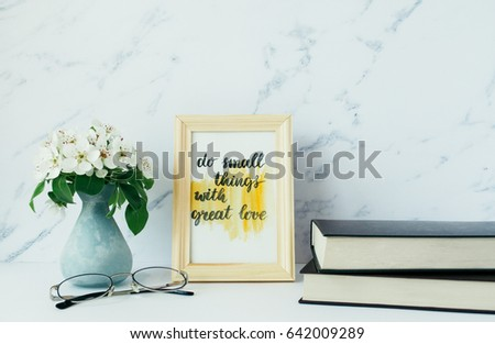 """Flowers of apple tree in vase, books, eyeglasses, card with inspiration quote """"do small things with great love"""" in a wooden photo frame. Minimalist white interior. Styled minimalistic still life #642009289"""
