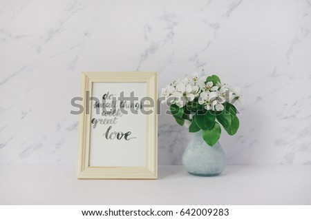 """Flowers of apple tree in vase, card with inspiration quote """"do small things with great love"""" in a wooden photo frame. Minimalist white interior. Styled minimalistic still life #642009283"""