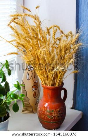 Flowers on a windowsill in pots a sheaf of wheat in a clay vessel