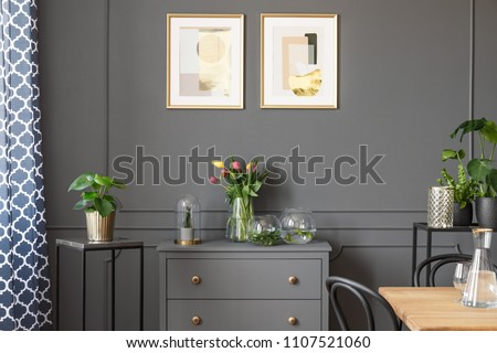 Flowers on grey cabinet under posters in minimal loft interior with plants. Real photo #1107521060