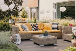 Flowers on rattan table near couch with patterned cushions on the terrace with lanterns. Real photo
