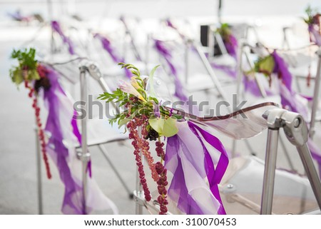 flowers on the chairs for a wedding ceremony