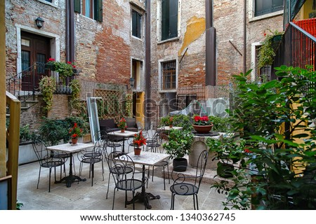 Flowers on the tables of a restaurant in a corner of Venice. History and romanticism. Italy. #1340362745