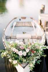 Flowers on white rowboat, floral arrangement decoration on small row boat on dock in lake or pond, wedding flower bouquet in wooden boat