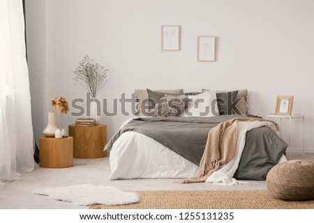 Flowers on wooden stool and pouf in white bedroom interior with posters above bed. Real photo