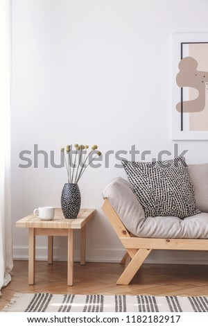 Flowers on wooden table next to beige couch with cushion in flat interior with poster. Real photo