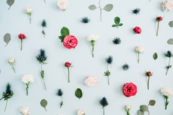 Flowers pattern texture made of beige and red roses, eucalyptus leaf on pale pastel blue background. Flat lay, top view. Floral texture background.