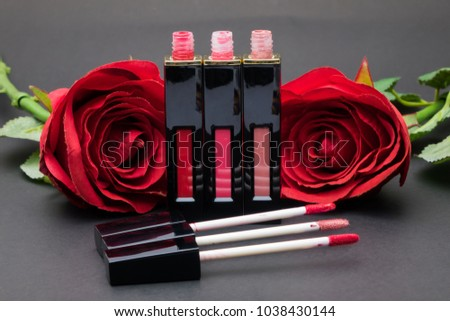 Stock Photo Flowers rose,Powder and Liquid lipstick brush uses lips for women,Beauty cosmetic black background. Makeup essentials item isolated on black background