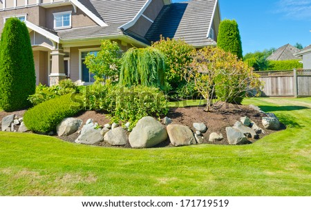 Flowers Stones And Nicely Trimmed Bushes In Front Of The