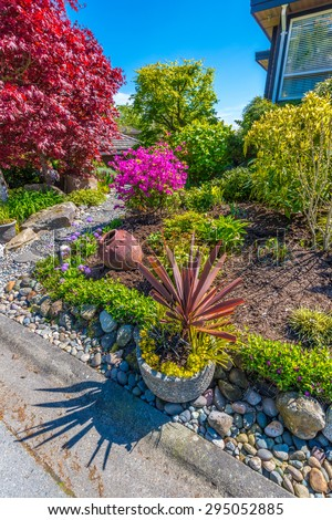 Flowers, stones and nicely trimmed bushes in front of the house, front yard. Landscape design. Vertical.