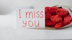 Flowers to a woman. Bouquet of red tulips and greeting card with handwritten inscription I miss you on a white background. Flowers delivery for valentine's day. Close-up
