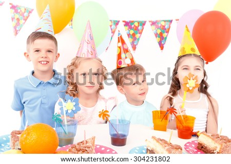 Flowers to girls. Two little cute boys and pair of pretty girls with toy flowers during birthday party.