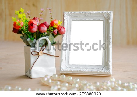 Flowers vase and blank white picture frame on wooden background, clipping path.