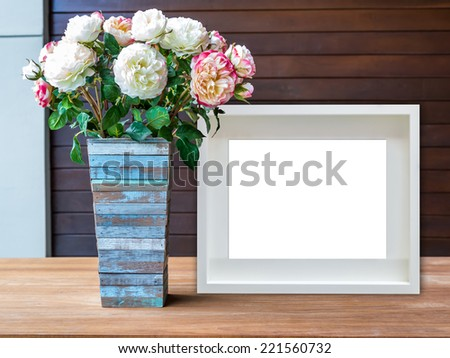 Flowers vase and blank white picture frame on wooden desktop