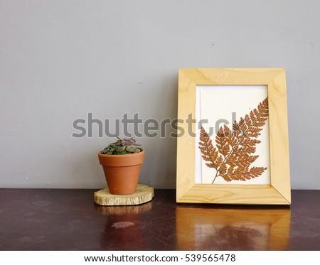 Flowers vase and wooden picture frame on wooden desktop