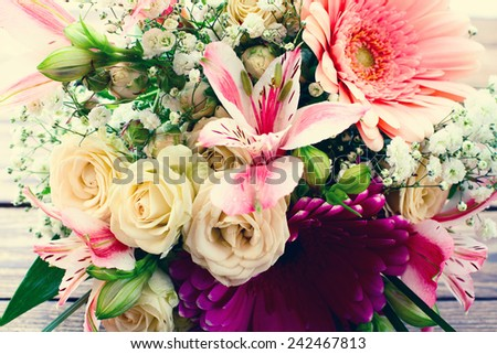 Flowers. Wedding bridal bouquet of white roses and pink lilies on  wooden table, close-up